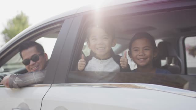 Ethnic family looking out car windows
