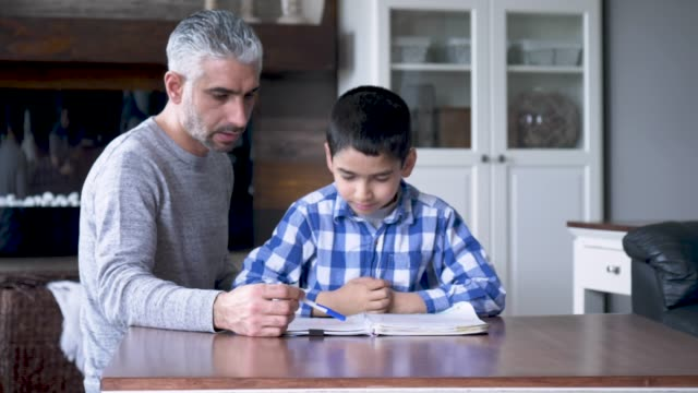 Ethnic father helping his son with homework A middle eastern man is helping his son with his school work in their living room at home. elementary age stock videos & royalty-free footage