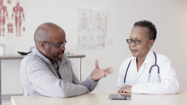 Ethnic Female Doctor Helping Her Adult Male Patient An older Asian doctor is going through a medical examination with her ethnic adult male patient in a hospital room. They are looking at a digital tablet together. nutritionist stock videos & royalty-free footage