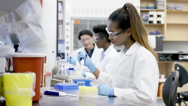 Ethnic female researcher transfers liquid sample solution