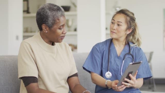 etniska kvinnliga senior få medicinsk kontroll upp - videor med medicinsk undersökning bildbanksvideor och videomaterial från bakom kulisserna