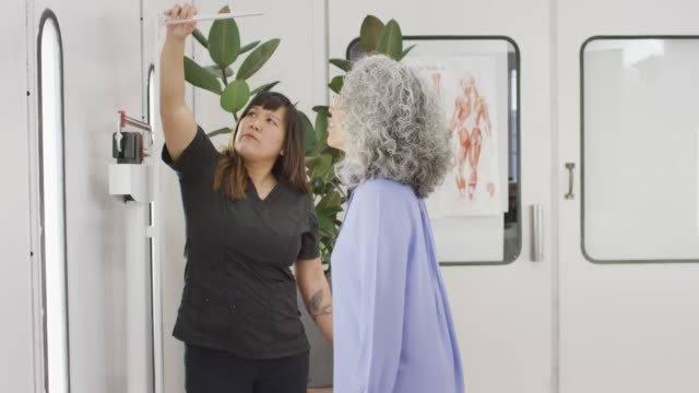 Ethnic Female Senior Having Her Height Measured Ethnic senior woman having her height measured by a woman of Filipino descent. The woman are inside a well lit medical office. measuring stock videos & royalty-free footage