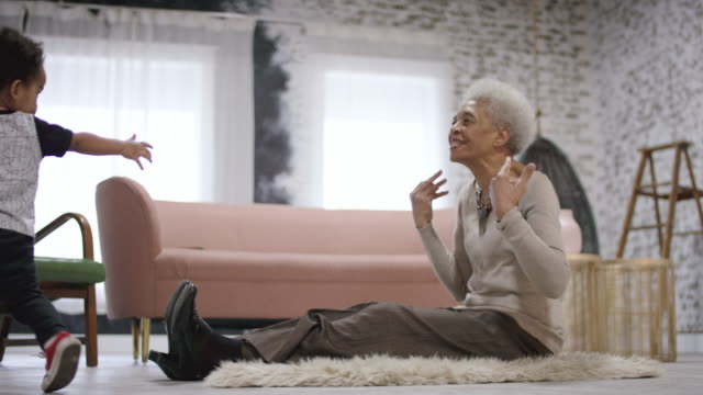 ethnic grandmother playing with her grandson - внук стоковые видео и кадры b-roll