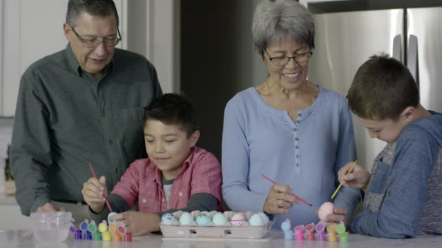 Ethnic Grandparents Painting Easter Eggs with Their Two Young Grandsons video
