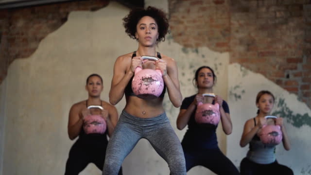 Ethnic group of young adult female group lifting weights in a fitness studio video