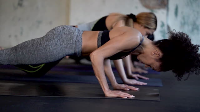 Ethnic group of young adult females doing planks and core exercises Ethnic group of young adult females doing planks and core and chest exercises inside of a studio physical position stock videos & royalty-free footage