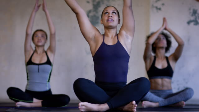 Ethnic group of young adult females group doing yoga in a fitness studio video