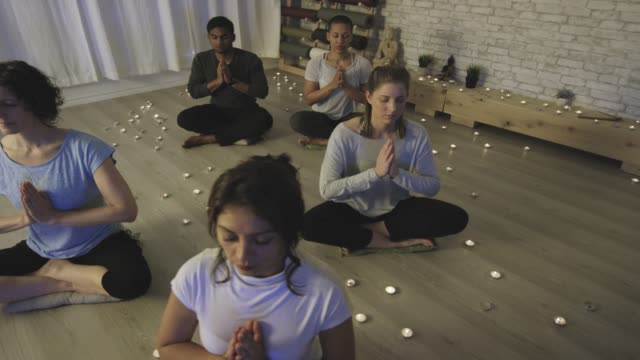 Ethnic group of young adults meditating together Several people are sitting in a meditation class with their eyes closed. They are lit by candlelight. mindfulness stock videos & royalty-free footage