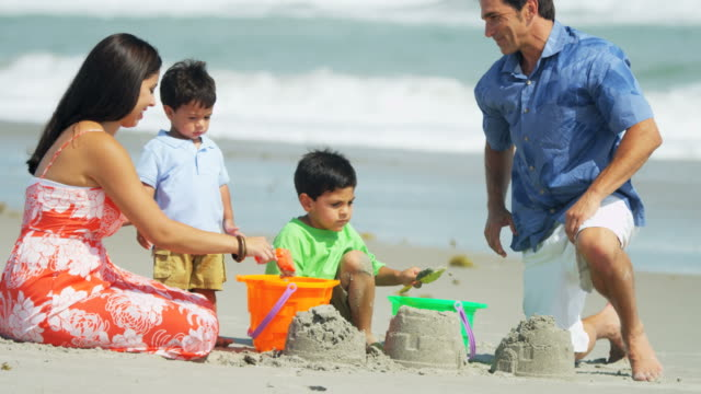 Ethnic Latino family fun making sandcastles on holiday video