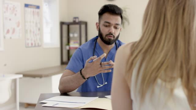 vidéos et rushes de infirmière mâle ethnique faisant le contrôle médical avec le patient féminin - infirmier