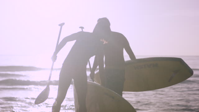 Ethnic man and woman entering water with SUP boards video