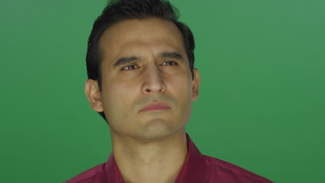 Ethnic man staring sadly at the camera, on a green screen studio background video