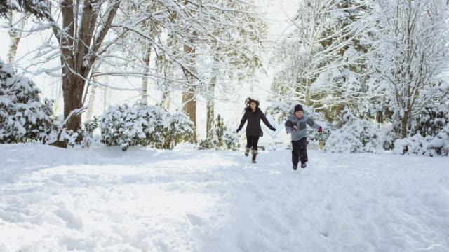 Ethnische Mutter mit ihren Söhnen laufen im Schnee – Video