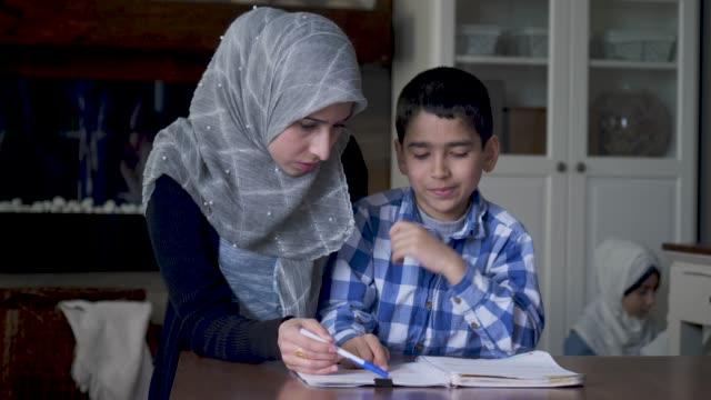 etnisk mamma hjälper sin son med läxor - working from home bildbanksvideor och videomaterial från bakom kulisserna