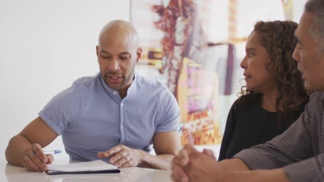 vídeos y material grabado en eventos de stock de pareja étnica senior con asesor financiero - propiedad inmobiliaria