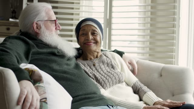 Ethnic Senior Female with Cancer Relaxes With Her Caucasian Husband An African American woman with cancer is wearing a headscarf and relaxing next to a window with her caucasian husband. They are laughing and smiling together. husband stock videos & royalty-free footage