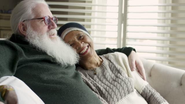 vidéos et rushes de femme aînée ethnique avec le cancer se détend avec son mari caucasien - courage