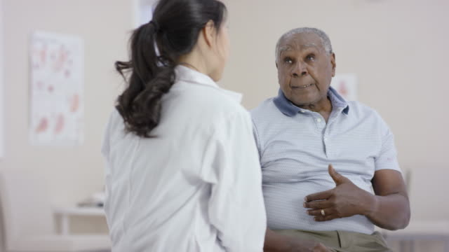 Ethnic senior man talking to a female doctor during an appointment A senior citizen of african descent goes to the doctor. He is gesturing that he is concerned about some health problems he has been experiencing. body care stock videos & royalty-free footage