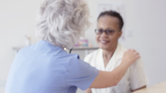 Ethnic Senior Patient Having Medical Checkup With Her Senior Aged Nurse A senior female caucasian nurse is going through a checkup with her female patient. The patient is an ethnic senior female. nutritionist stock videos & royalty-free footage