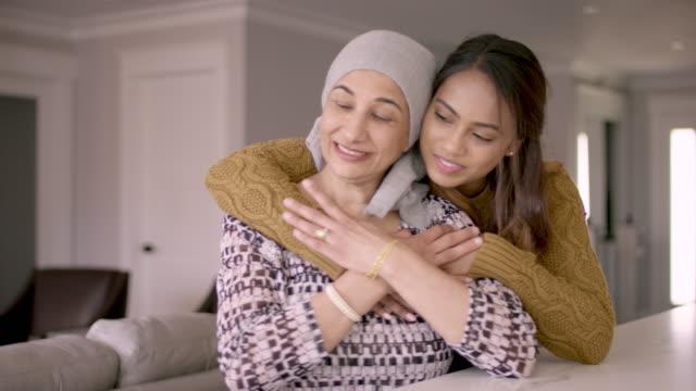 がんを持つエスニックシニア女性が娘に抱きつかれる - 回復点の映像素材/bロール