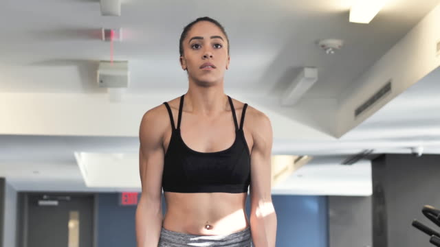 Ethnic Young Adult female doing bicep curls at the gym with weights