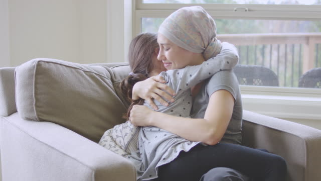 Ethnic Young Adult Female with Cancer Holding a Young Girl video