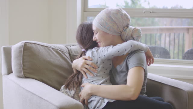 Ethnic young adult female with cancer hugging her daughter video