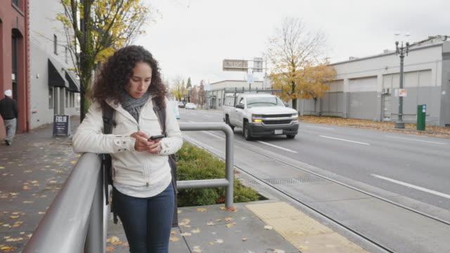 stockvideo's en b-roll-footage met etnische vrouwelijke jongvolwassene wacht op tram - bushalte