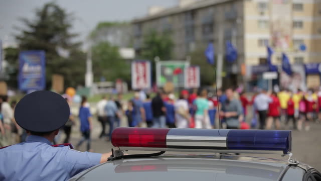 Euro 2012 Ukraine Police car standing at crowd out of focus in background. police meeting stock videos & royalty-free footage