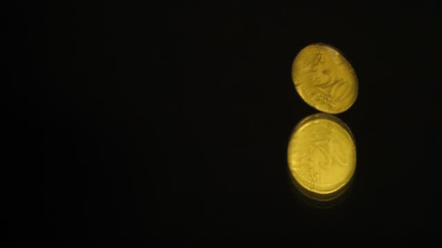 20 Euro cents Coin is rotating on a black mirror