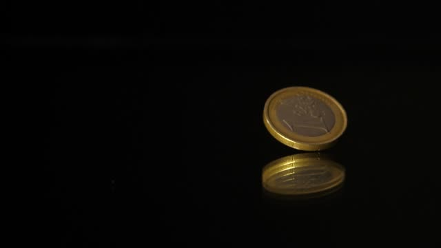 1 Euro coin falls on a black mirror