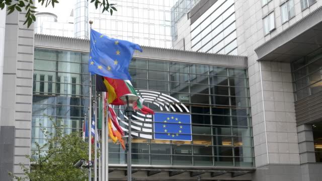 europäische und eu-flaggen außerhalb des eu-parlaments in brüssel - europäische union stock-videos und b-roll-filmmaterial
