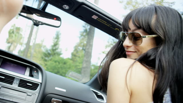European brunette dancing singing and clapping in cabriolet