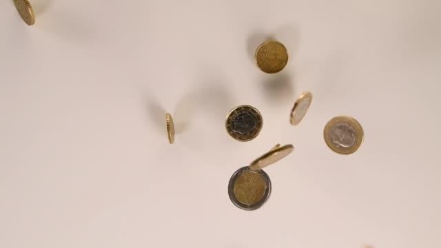 European coins falling on white background