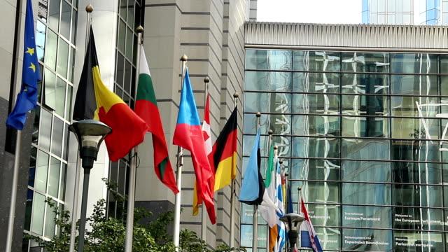 stockvideo's en b-roll-footage met europese landen vlaggen europa parlement hoofdkwartier in brussel. mooi shot van europa, cultuur en landschappen. reizende bezienswaardigheden, toeristische bezienswaardigheden van de standpunten van belgië. wereld reizen, west europese reis stadsgezicht, buiten schot - estland