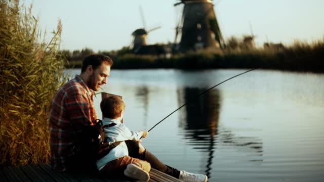 stockvideo's en b-roll-footage met europese vader en zoon zitten samen op lake pier. jongen houdt een handgemaakte visserij aan te pakken. gelukkig familierelaties. 4k - netherlands