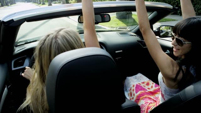European female friends driving luxury open top car