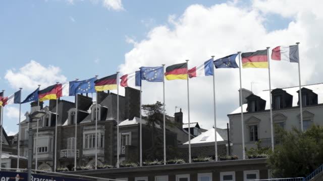 美しいコテージと青く曇った空を背景に風に揺れるヨーロッパの旗。ストック映像。家々の前でドイツ、フランス、欧州連合の旗 ビデオ