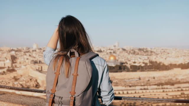 European girl with grey backpack enjoys Jerusalem. Female tourist looks at ancient old town in Israel from a skydeck. 4K video