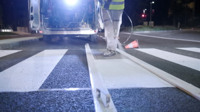 European Infrastructure Crew Repainting Road Markings Low angle view of construction crew upgrading arrow marking on Central European urban street with fresh spray paint. civil engineering stock videos & royalty-free footage