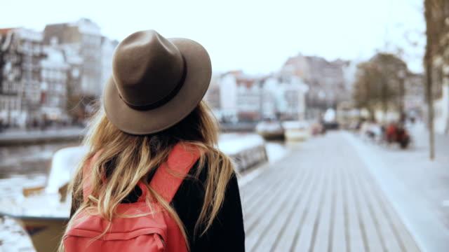 European lady tourist walks near river with phone. Pretty traveler female looks around walking along a river quay. 4K