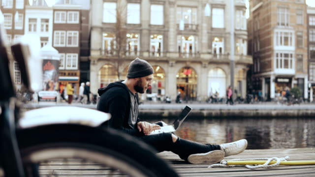 4K European man sitting with laptop in the street. Bicycle wheel in front of camera. Creative arts worker mobile office video