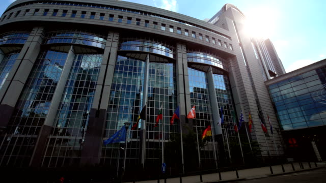 europäischen parlament in brüssel. deutsche flagge verschoben auf die hälfte. - europäische union stock-videos und b-roll-filmmaterial