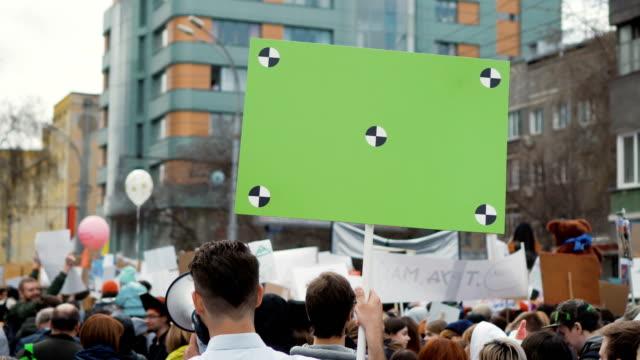 vídeos y material grabado en eventos de stock de popular europeo en la demostración. hombre con un cartel gritando en una boquilla. - político