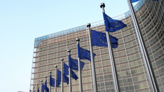 european union flags at berlaymont building - european commission building in brussels - quartiere generale video stock e b–roll