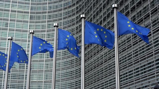 vidéos et rushes de 4k. drapeaux de l'union européenne dans une rangée agitant dans le vent, commission européenne - europe