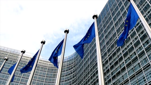 European Union flags waving in the wind in slow motion video