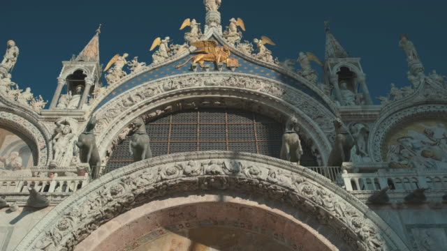 European vacation. Facade of a Saint Marco cathedral in Venice. Beautiful art on building's facade. Columns and archs European vacation. Facade of a Saint Marco cathedral in Venice. Beautiful art on building's facade. Columns and archs. neo gothic architecture stock videos & royalty-free footage