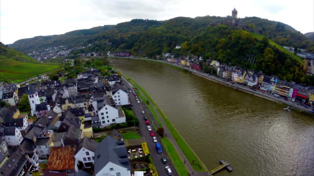 European village aerial, colored house roof tops, river ships. Beautiful aerial shot above Europe, culture and landscapes, camera pan dolly in the air. Drone flying above European land. Traveling sightseeing, tourist views of Germany. video