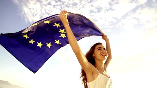 European Woman holding EU flag against sky waving video